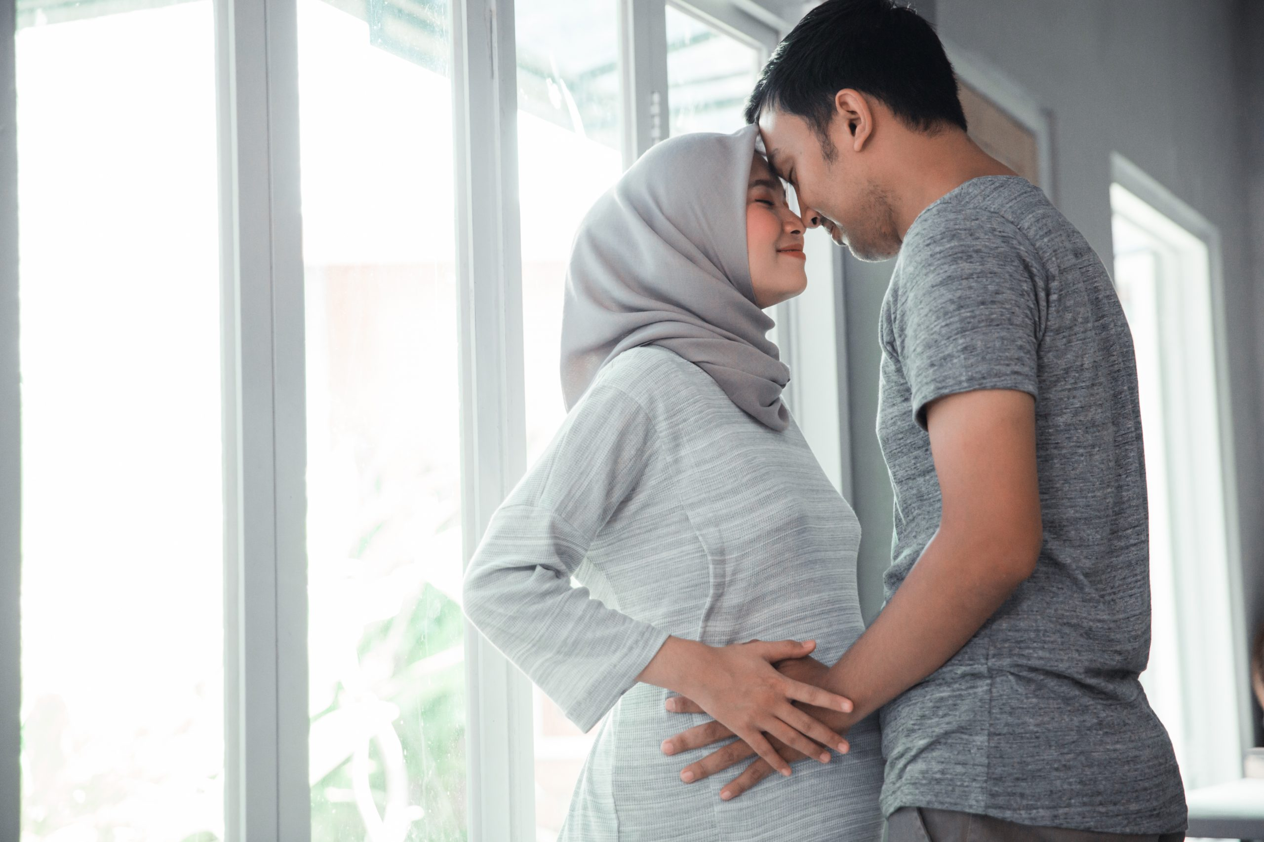 asian muslim pregnant woman with her husband hold on tummy at home